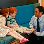 Kids dentist Dr Darryl Marsh, talking to 2 kids sitting on a chair