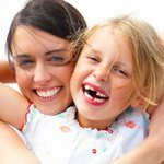 Mother and daughter all smiles with daughter's 2 front teeth missing