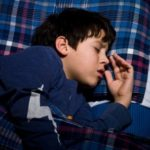 young boy sleeping experiencing teeth grinding