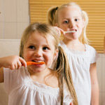 2 young girls brushing teeth